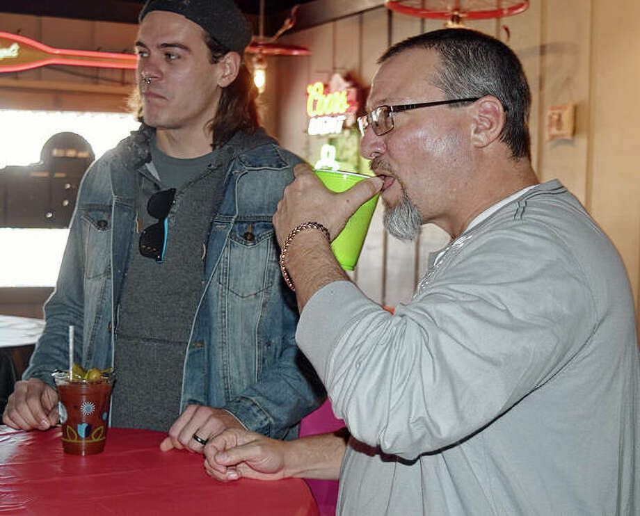 Nick Kriner (left) and Craig Miller, both of Macon, enjoy drinks during a New Year's Day party Wednesday at The HandleBar Pizza & Pub in Jacksonville. Photo: Marco Cartolano | Journal-Courier