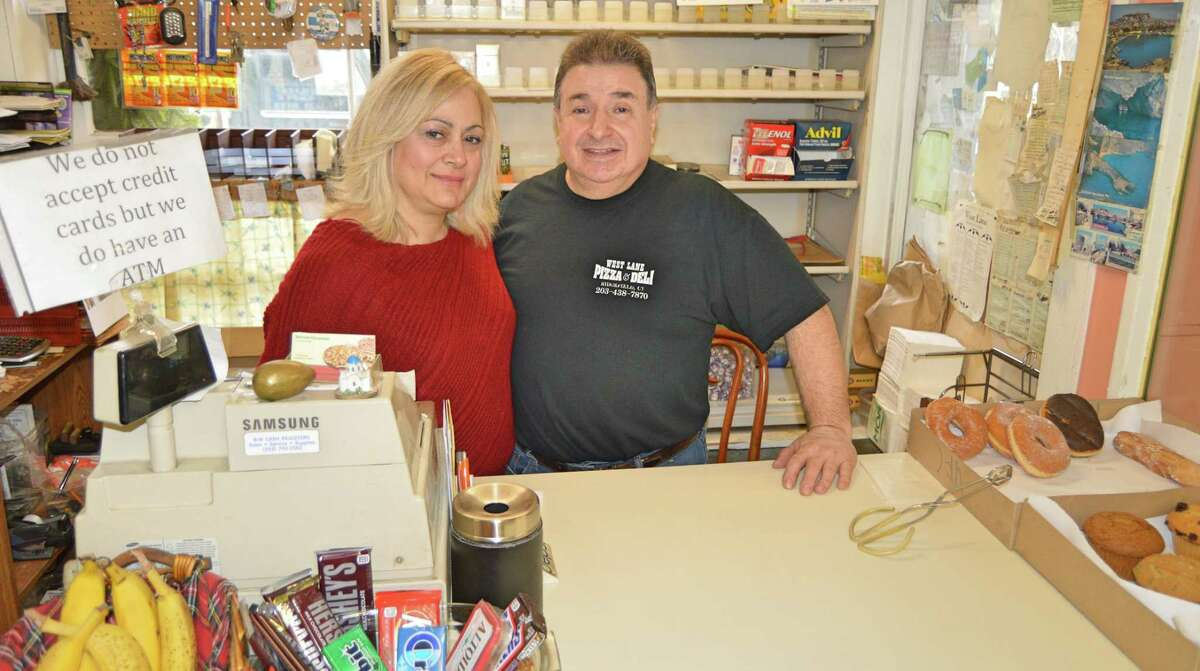 Owners John and Anna Saoulidis behind the cash register at West Lane Pizza and Deli.