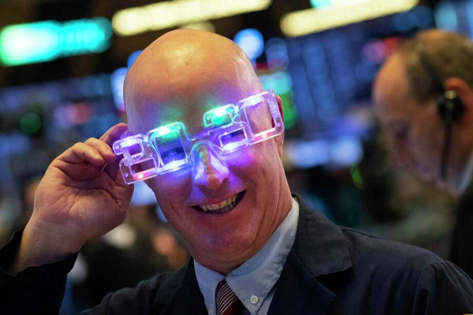 Stock trader John O'Hara tries on his New Year's 2020 party glasses at New York Stock Exchange, Tuesday, Dec. 31, 2019. Stocks slipped globally in quiet New Year's Eve trading Tuesday with many markets closed. Wall Street could close 2019 with back-to-back daily losses in a year that the U.S. posted the largest market gains since 2013. Photo: Mark Lennihan / Associated Press / Copyright 2019 The Associated Press. All rights reserved
