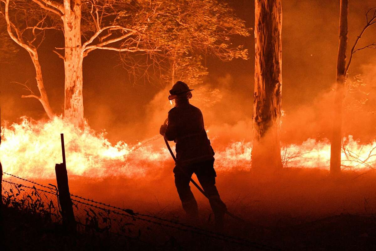 This picture taken on December 31, 2019 shows a firefighter hosing down trees and flying embers in an effort to secure nearby houses from bushfires near the town of Nowra in the Australian state of New South Wales. - Fire-ravaged Australia has launched a major operation to reach thousands of people stranded in seaside towns after deadly bushfires ripped through popular tourist areas on New Year's Eve.
