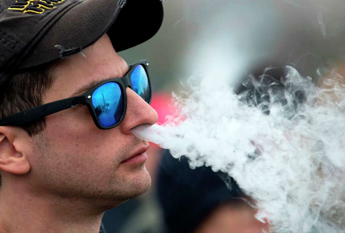 A demonstrator vapes during a consumer advocate groups and vape storeowners rally outside of the White House to protest the proposed vaping flavor ban in Washington, DC.