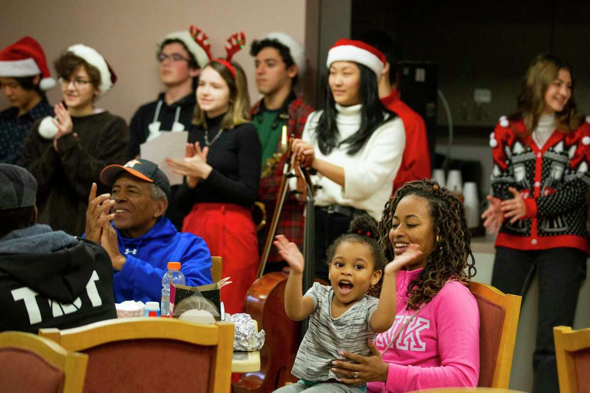 Meilani Saunders, 3, applauds as she listens to christmas songs on the arms of her mother Teri Saunders, 33, during a visit to Saunders' grandfather coach John Wilkerson, left, at the St Dominic Village, a Senior Care Community on Saturday, Dec. 21, 2019, in Houston.