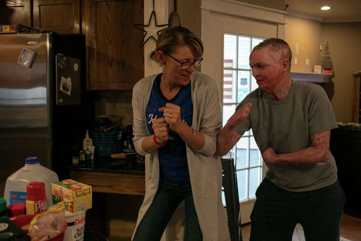 """Zachary Sutterfield wrestles with his mom, Deona Jo """"DJ"""" Sutterfield, as they make dinner at their San Angelo home. The family was able to celebrate Christmas at home for the first time since Zach suffered critical injuries in a deadly San Marcos apartment fire 18 months ago."""