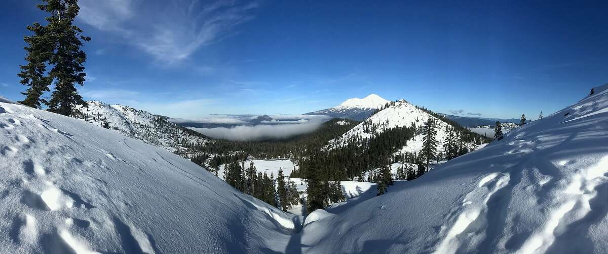 From an overlook near Heart Lake in the Trinity Divide, snowshoe trekkers can take in a panorama that extends for miles to Mount Shasta
