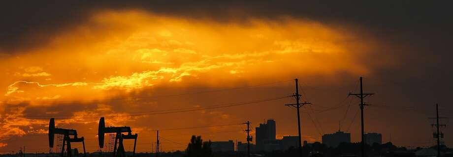 The sun sets behind the Midland skyline as pumpjacks work outside the city limits Thursday, Sept. 15, 2016. ( Michael Ciaglo / Houston Chronicle ) Photo: Michael Ciaglo/Houston Chronicle