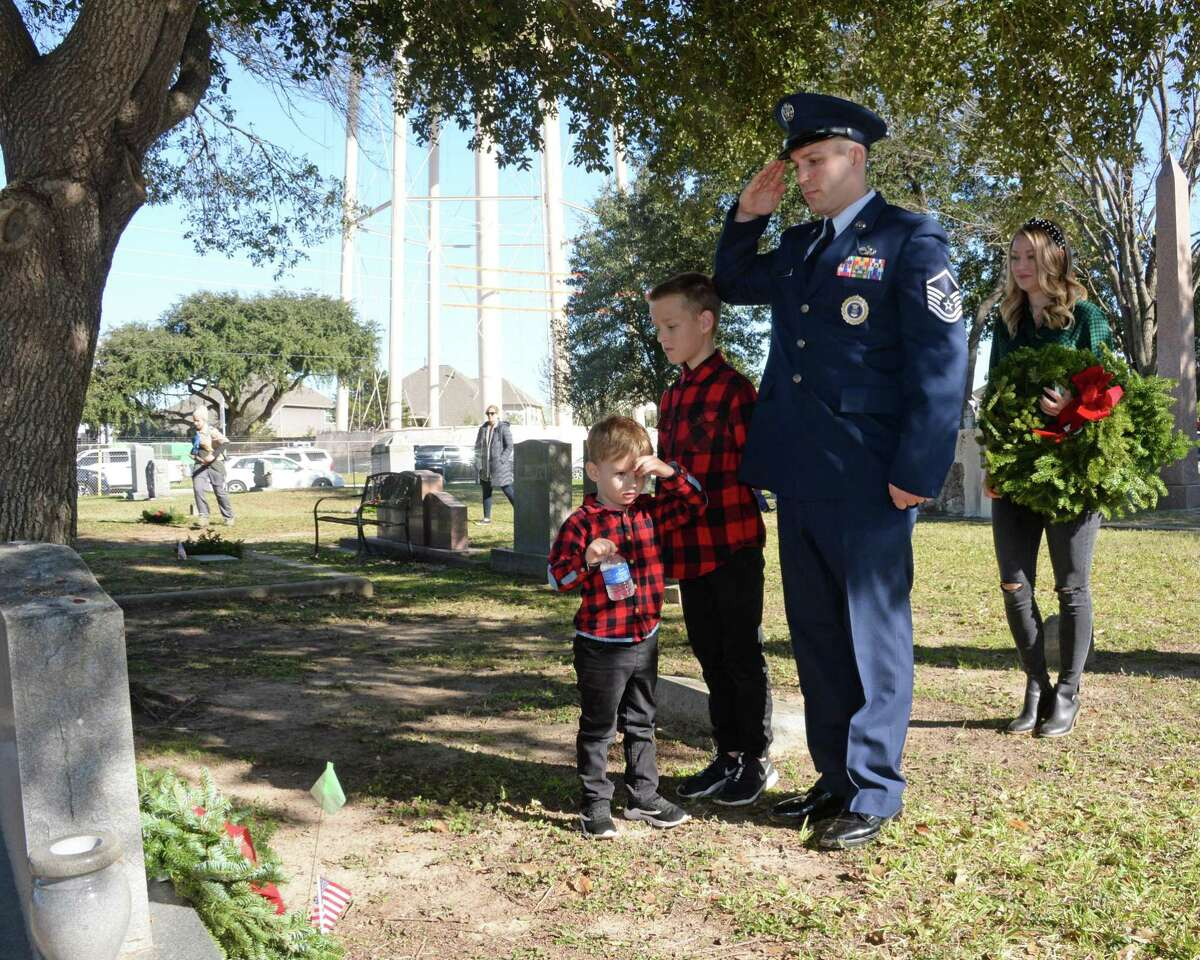 Kyle Atkinson, with assistance of sons Case, 3, and Kyler, 10 salutes after placing a wreath on a grave during the National Wreaths Across America Ceremony at Magnolia Cemetery, Saturday, December 14, 2019 in Katy, TX.