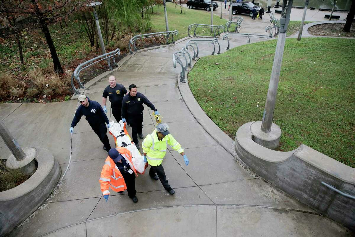 Members of the Houston Police Dept. and Medical Examiners office remove a body discovered in the Buffalo Bayou on Thursday, Jan. 2, 2020 in Houston.
