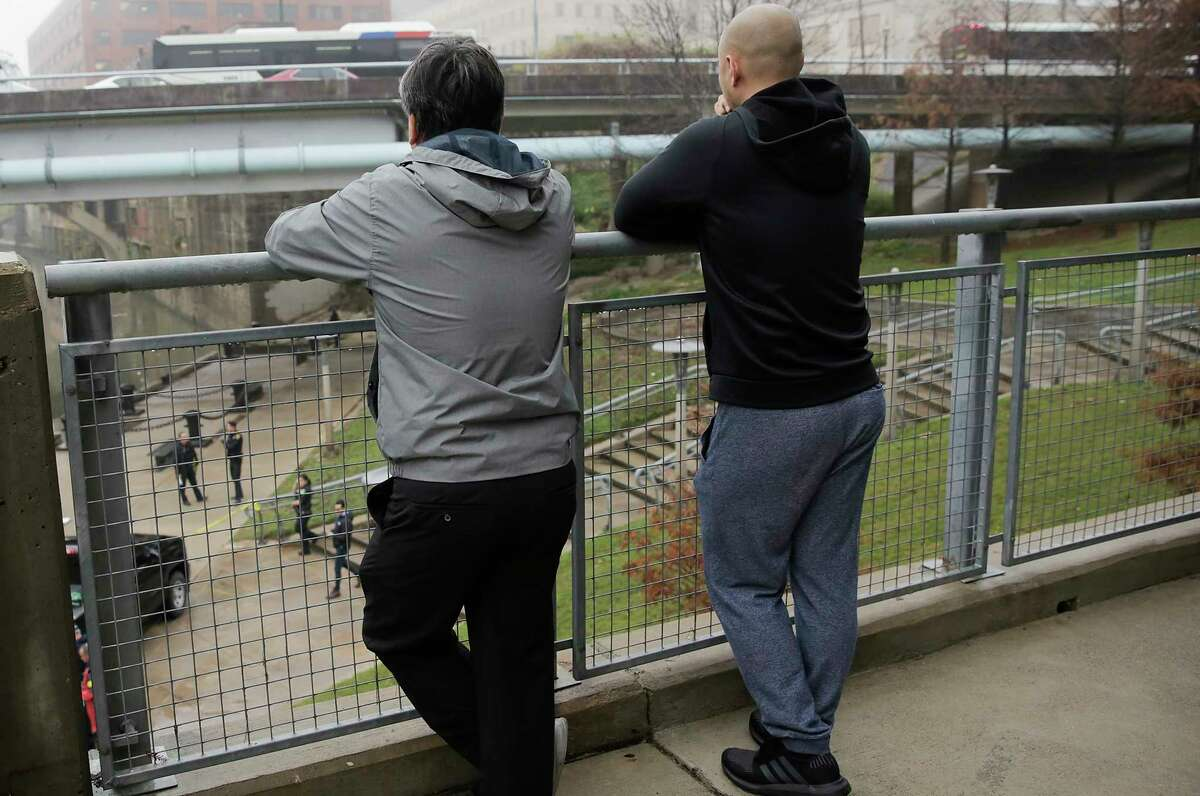 Onlookers watch as the Houston Police pull out a body discovered in the Buffalo Bayou on Thursday, Jan. 2, 2020 in Houston.