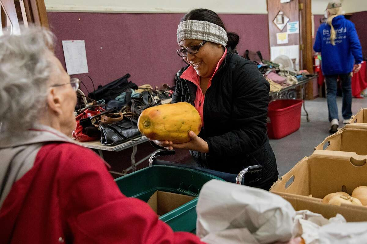 Beatrice Rivera of Paradise picks out a papaya while making her way through the aisles of the Donation Center for victims of the Camp Fire at the Magalia Community Church in Magalia, Calif. Tuesday, December 17, 2019. Although the Camp Fire happened more than a year ago, many victims have yet to rebuild their lives and homes.