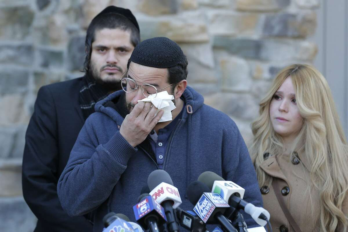 Surrounded primarily by family, David Neumann, center, wipes his eyes as he speaks to reporters in New City, N.Y., Thursday, Jan. 2, 2020, about his father, Josef Neumann who was critically injured in an attack on a Hanukkah celebration. Nicky Cohen, Josef Neumann's daughter, told reporters she hopes her father regains consciousness and finds a changed world while making an emotional plea to end hatred and anti-Semitism. Their 72-year-old father has been unconscious since he was wounded Saturday in a machete attack at a rabbi's home in Monsey, N.Y.