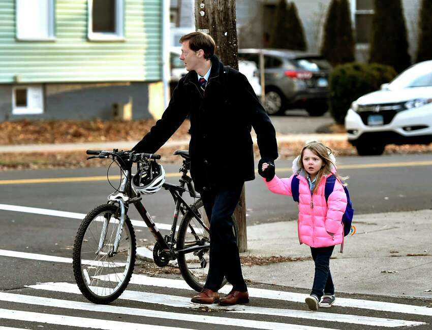 New Haven, Connecticut - Thursday, January 2, 2020: New Haven Mayor Justin Elicker walks his daughter Molly, 5, to the school bus stop Thursday morning on the corner of Orange Ave. and Canner St. in New Haven before riding his bicycle to New Haven City Hall on his first day on the job as Mayor.