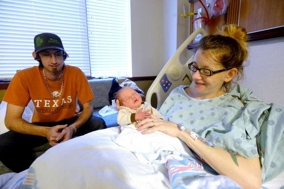 Amber Blankenship cuddles with newborn daughter Zarya Sky Williamson as father Brandon Williamson looks on while in their room at Christus St. Elizabeth Hospital Thursday. Zarya was born early New Year's Day. Photo taken Thursday, January 2, 2020 Kim Brent/The Enterprise Photo: Kim Brent/The Enterprise