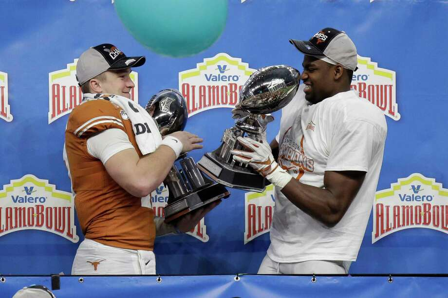 Texas quarterback Sam Ehlinger, left, and linebacker Joseph Ossai, right, celebrate the team's win over Utah in the Alamo Bowl NCAA college football game in San Antonio, Tuesday, Dec. 31, 2019. Ehlinger was named offensive player of the game, and Ossai outstanding defensive player. (AP Photo/Austin Gay) Photo: Austin Gay, FRE / Associated Press / Copyright 2019 The Associated Press. All rights reserved.
