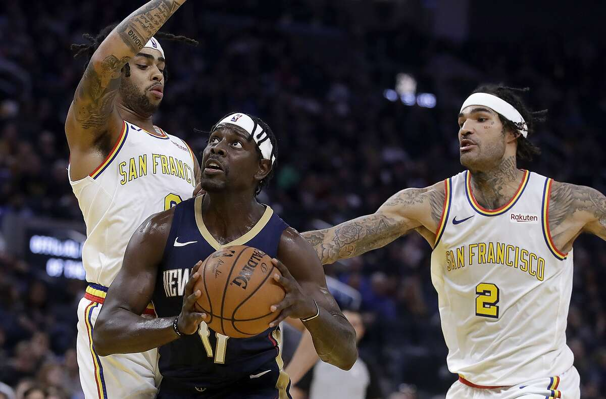 New Orleans Pelicans' Jrue Holiday, center, drives the ball between Golden State Warriors' D'Angelo Russell, left, and Willie Cauley-Stein during the first half of an NBA basketball game Friday, Dec. 20, 2019, in San Francisco. (AP Photo/Ben Margot)