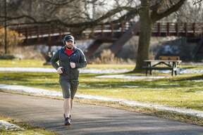 Josh Wright jogs along the rail trail near the Tridge Thursday, Jan. 2, 2020. (Katy Kildee/kkildee@mdn.net)