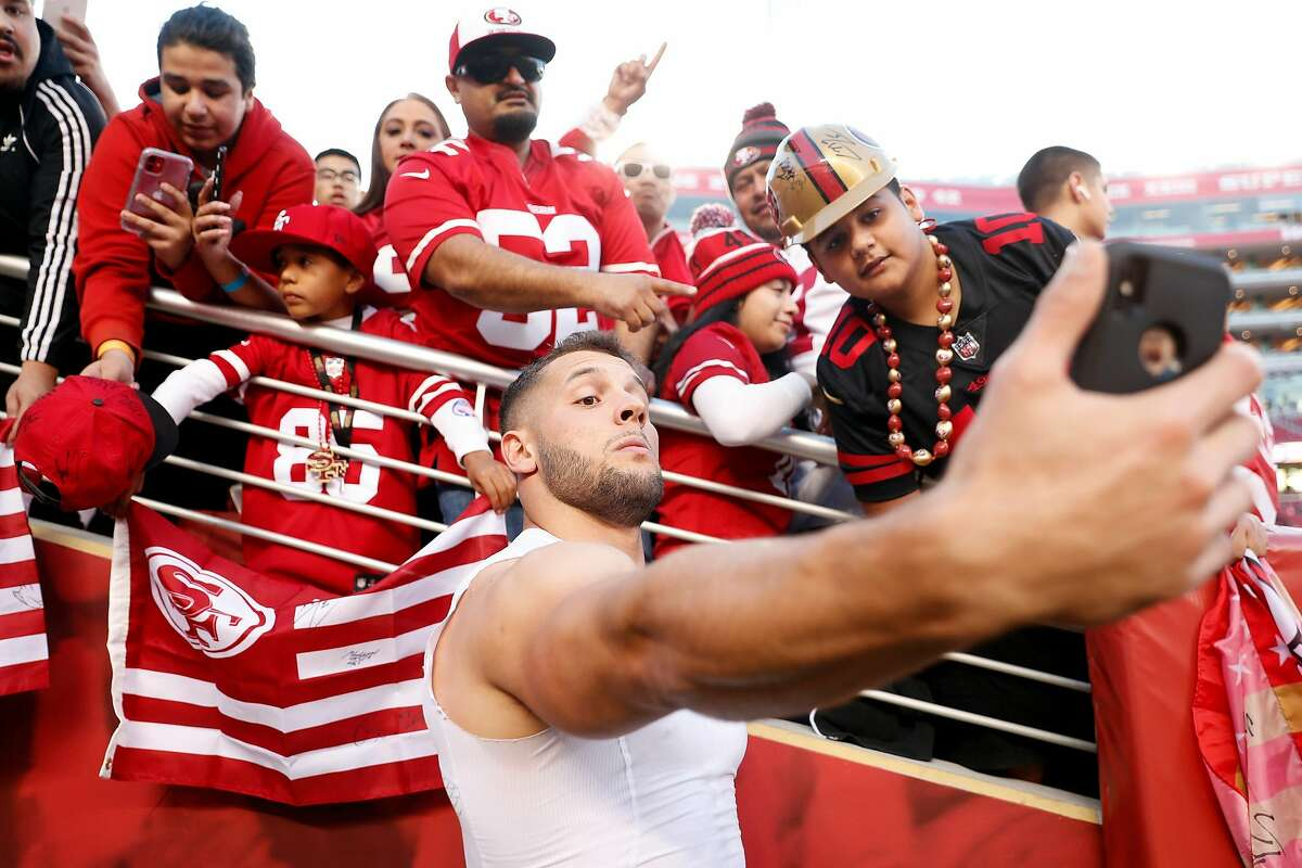 San Francisco 49ers' Nick Bosa takes a selfie with a fan's phone before playing Green Bay Packers during NFL game at Levi's Stadium in Santa Clara, Calif., on Sunday, November 24, 2019.