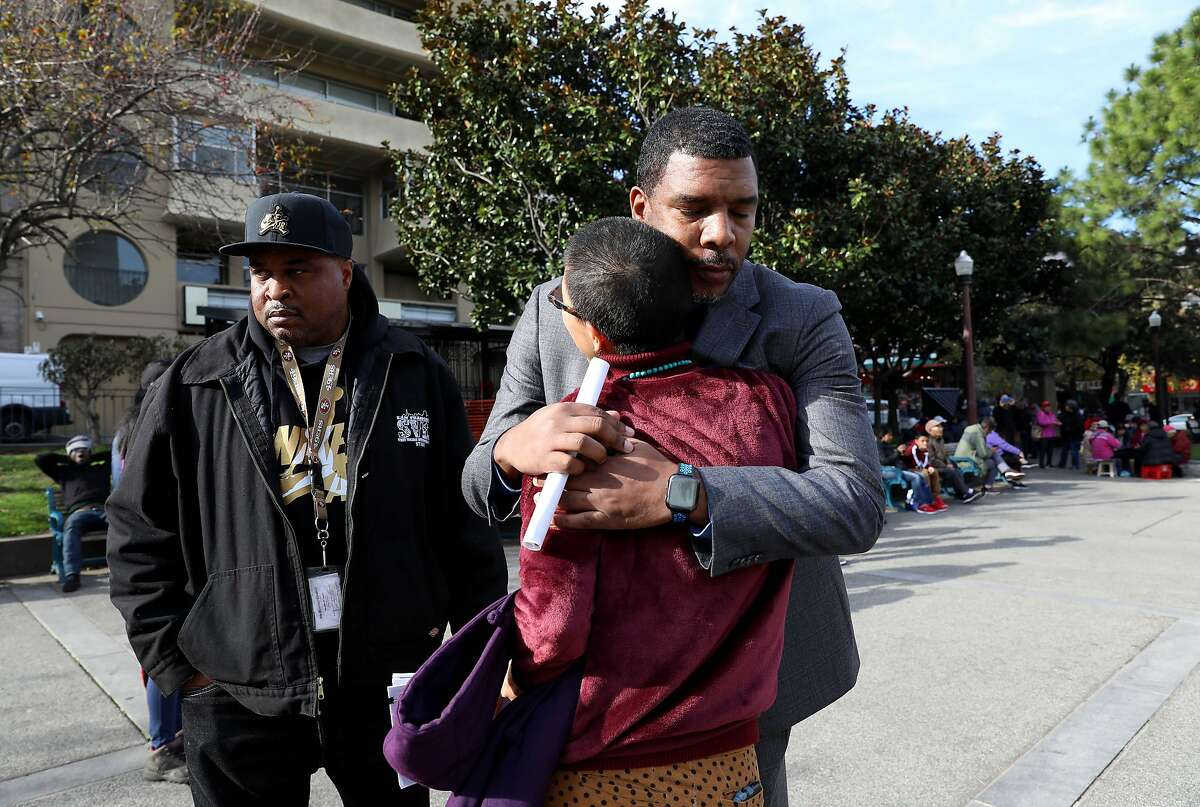 James Caldwell, right, Crisis Response Manager, Street Violence Intervention Program (SVIP), hugs Sasanna Yee, a community healer and organizer, as Victor Jones, a staff member at SVIP (left), stands nearby while the group meets at Chinatown's Pourtsmouth Square in San Francisco, Calif., on Tuesday, December 31, 2019. SVIP has helped intervene in neighborhood trouble driving down violence and homicides in San Francisco to an all time low in 2019. It's been patrolling Chinatown, where in recent weeks there have been a number of high-profile, high-violence incidents, including one in which an elderly man was beaten by a group of four to six much younger men, apparently unprovoked. The SVIP team has been working Chinatown to increase it's presence there in an effort to prevent any further violence.