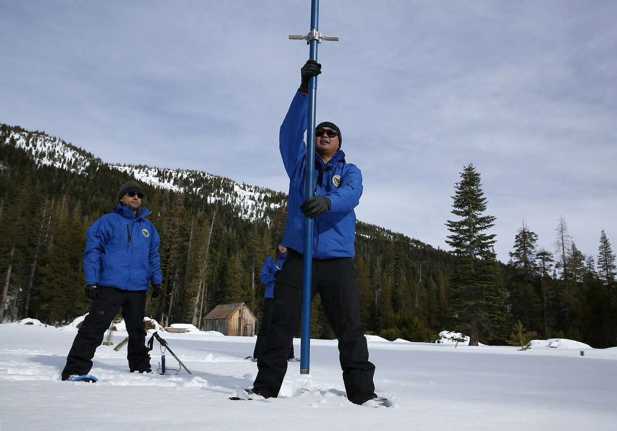 Sean de Guzman, right, chief of snow surveys for the California Department of Water Resources, plunges a snow survey tube into the snowpack during the first snow survey of the season at Phillips Station near Echo Summit, Calif., Thursday, Jan. 2, 2020. The survey found the snowpack at 33.5 inches deep with a water content of 11 inches which is 97% of average at this location at this time of year. Also seen are DWR's Ramesh Gautam, left, and Lauren Miller, behind de Guzman. (AP Photo/Rich Pedroncelli)