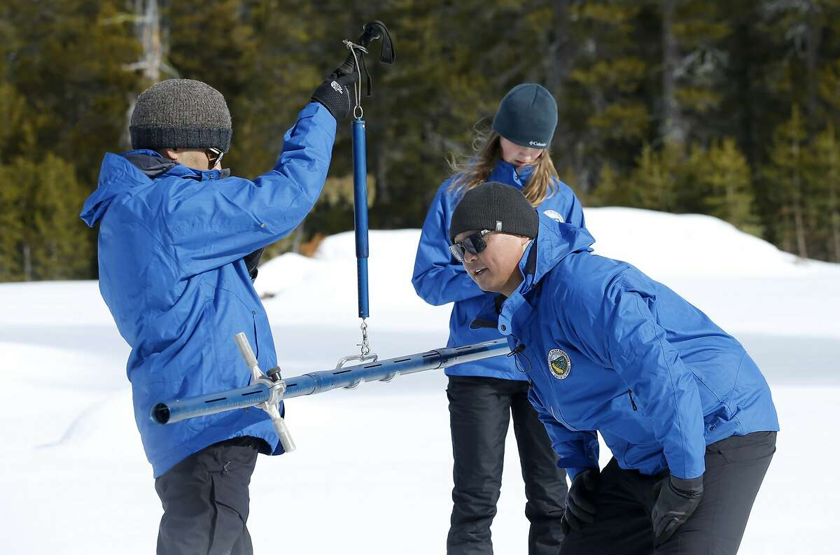Sean de Guzman, center, chief of snow surveys for the California Department of Water Resources, checks the weight of a snow sample on a scale held by DWR's Ramesh Gautam, left, as DWR's Lauren Miller, background records the information during the first snow survey of the season at Phillips Station near Echo Summit, Calif., Thursday, Jan. 2, 2020. The survey found the snowpack at 33.5 inches deep with a water content of 11 inches which is 97% of average at this location at this time of year. (AP Photo/Rich Pedroncelli)