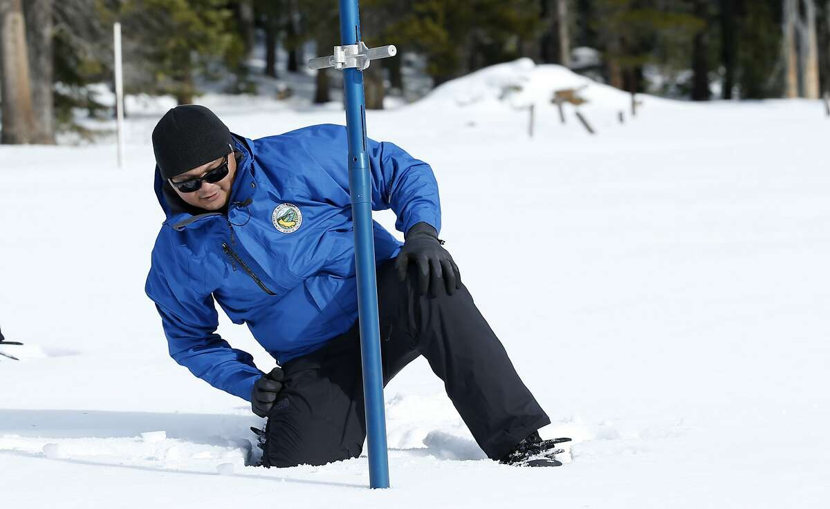 Sean de Guzman, chief of snow surveys for the California Department of Water Resources, checks the depth of the snowpack during the first snow survey of the season at Phillips Station near Echo Summit, Calif., Thursday, Jan. 2, 2020. The survey found the snowpack at 33.5 inches deep with a water content of 11 inches which is 97% of average at this location at this time of year. (AP Photo/Rich Pedroncelli)