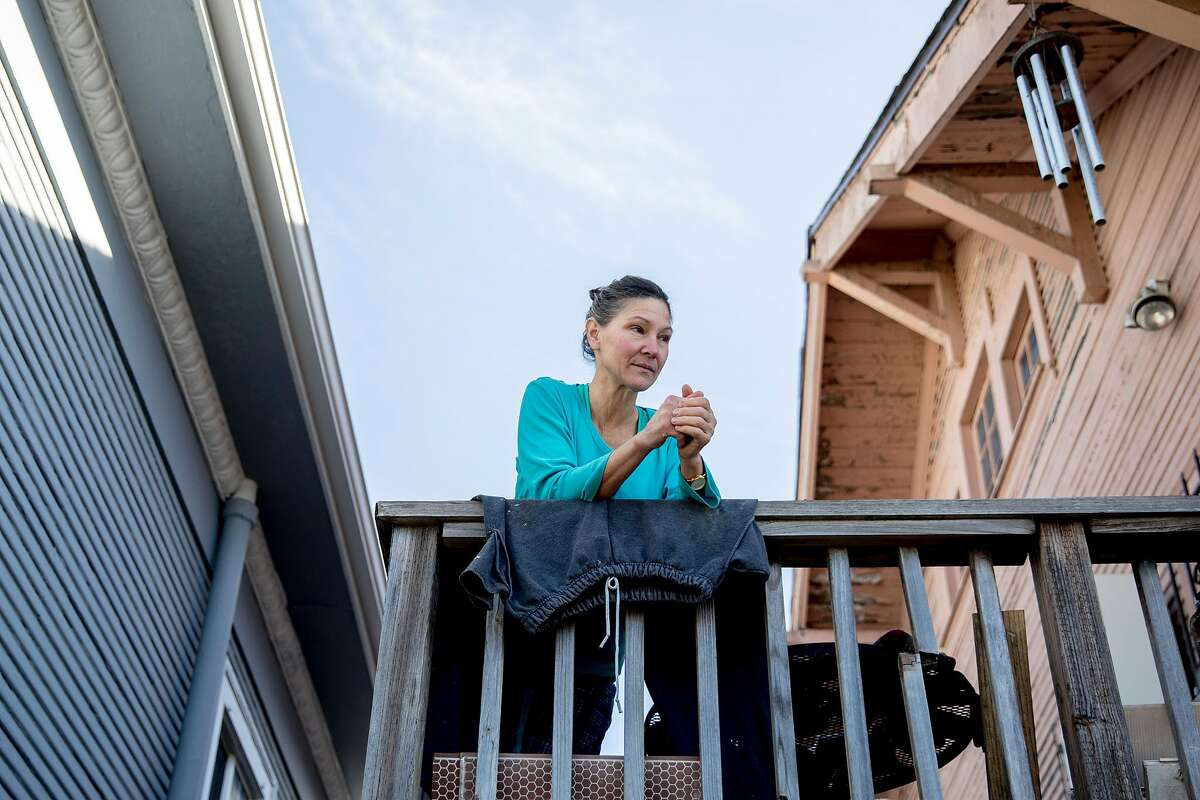 Mariah Cochrane looks out from her balcony near the corner of West and Apgar streets in Oakland, Calif. Thursday, January 2, 2020 neighboring where a warehouse fire broke out in the early morning hours of Friday, Dec. 27, 2019.