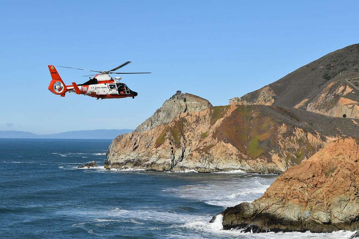 A helicopter searches for a vehicle that was seen launching off the side of Highway 1 in San Mateo County on Dec. 30. Neither the car nor any occupants have been found.