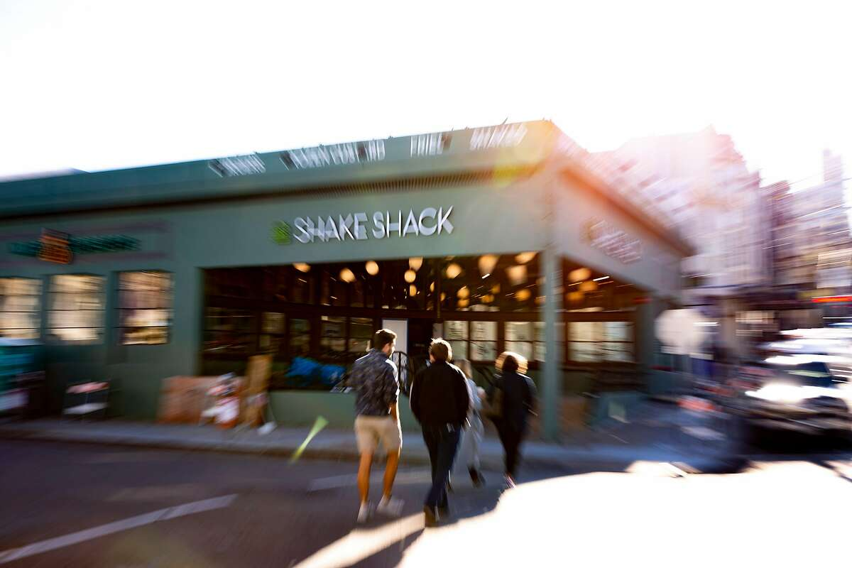 People walk past the Shake Shack located at 3060 Fillmore Street on Thursday, Dec. 26, 2019, in San Francisco, Calif.