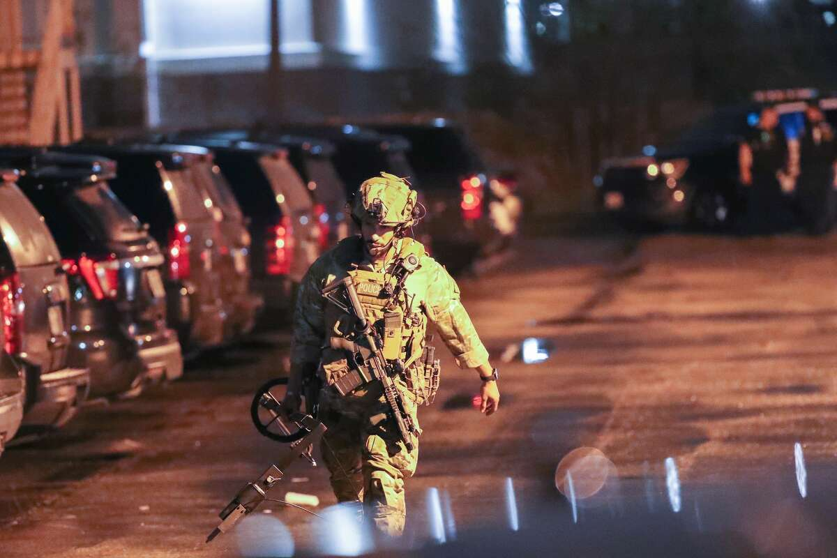 A Houston police SWAT officer walks outside a hotel where a wanted man held two women hostage on Thursday, Jan. 2. The man peacefully surrendered.
