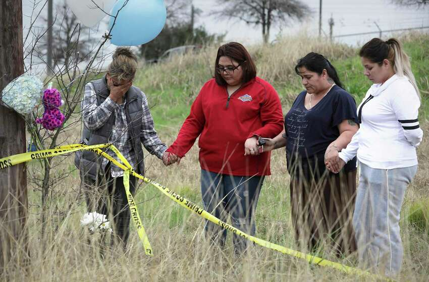 Mourners Sylvia Santana, left to right, Diamond Moreno, Margarita Santoya and Mary De La Rosa pray after placing flowers, balloons and stuffed toys on Jan. 11, 2019, near the site where authorities found the body of 8-month-old King Jay Davila wrapped in a blanket and buried in a backpack next to Rosillo Creek by Rittiman Road.