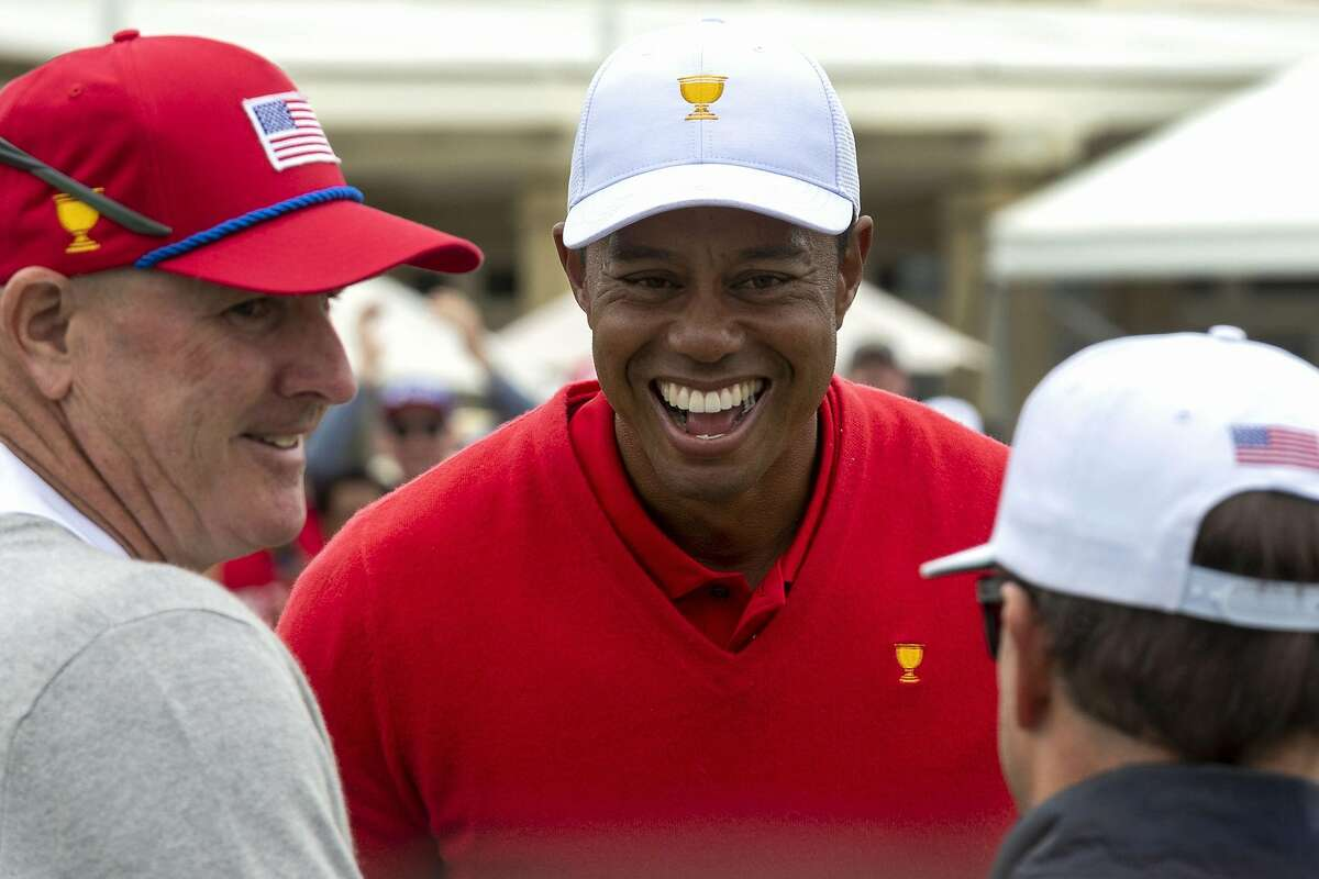 US team captain Tiger Woods (C), US player Zach Johnson (R) and caddy Joe LaCava (L) speak after Woods won his match on the final day of the Presidents Cup golf tournament in Melbourne on December 15, 2019. (Photo by SIMON BAKER / AFP) / -- IMAGE RESTRICTED TO EDITORIAL USE - STRICTLY NO COMMERCIAL USE -- (Photo by SIMON BAKER/AFP via Getty Images)