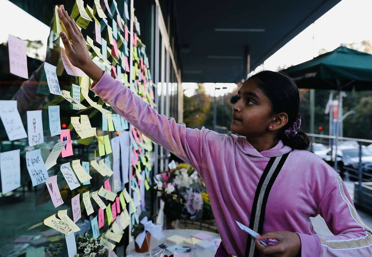 Anushka Reddy, 10, of Pleasanton, adheres a post-in note to a window at Starbucks, located at 2080 Mountain Blvd., in Montclair, Calif., on Wednesday, January 2, 2020. Two days prior, on New Year's Eve, a man was critically injured outside the coffee shop after he chased the thief who stole his laptop. The man later died of his injuries as a result of the incident. The Oakland Police Department announced on New Year's Day that two men had been arrested in connection with Tuesday's episode.