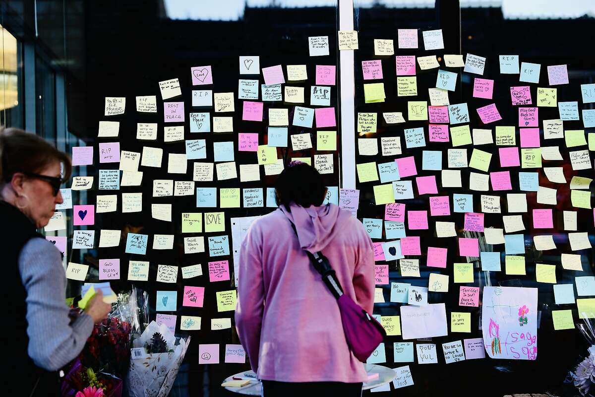 Sue Graham, left, of Upper Rockridge, and Anushka Reddy, 10, of Pleasanton, stand in front of post-it notes left in memory of a customer who was critically injured at Starbucks, located at 2080 Mountain Blvd., in Montclair, Calif., on Wednesday, January 2, 2020. Two days prior, on New Year's Eve, the man was critically injured outside the coffee shop after he chased the thief who stole his laptop. The man later died of his injuries as a result of the incident. The Oakland Police Department announced on New Year's Day that two men had been arrested in connection with Tuesday's episode.