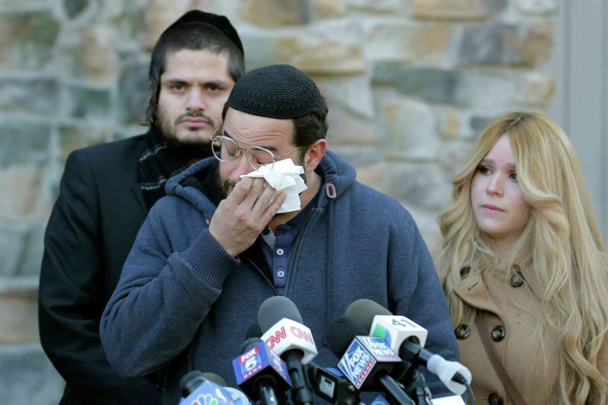 Surrounded primarily by family, David Neumann, center, wipes his eyes as he speaks to reporters in New City, N.Y., Thursday, Jan. 2, 2020, about his father, Josef Neumann who was critically injured in an attack on a Hanukkah celebration. Nicky Cohen, Josef Neumann's daughter, told reporters she hopes her father regains consciousness and finds a changed world while making an emotional plea to end hatred and anti-Semitism. Their 72-year-old father has been unconscious since he was wounded Saturday in a machete attack at a rabbi's home in Monsey, N.Y. (AP Photo/Seth Wenig)