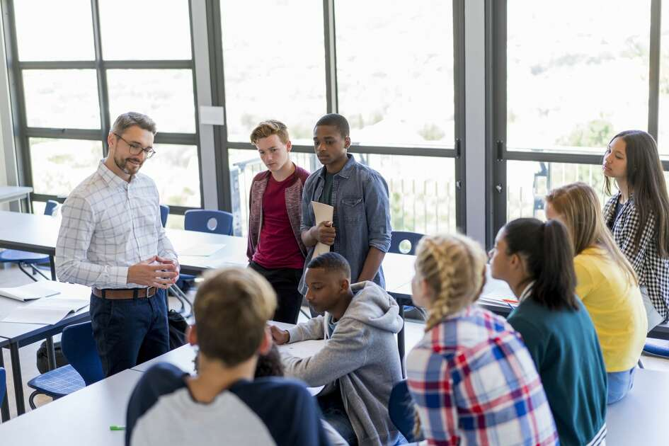 High angle view of professor is teaching in classroom. Multi-ethnic students and male teacher are discussing at school. They are wearing casuals in high school building.