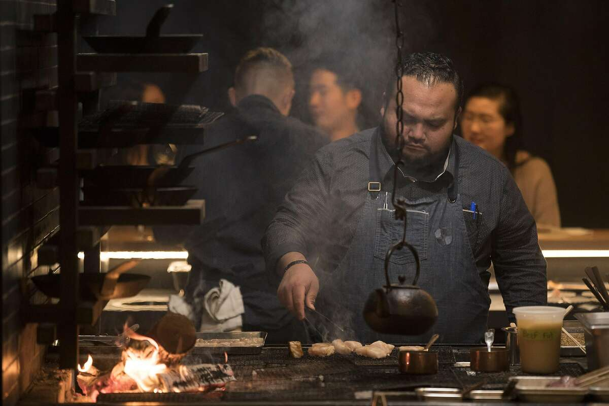 A cook works on a dish at the wood grill at Gozu restaurant where one of the specialties is Wagyu beef in San Francisco, Calif., on Wednesday, December 18, 2019.