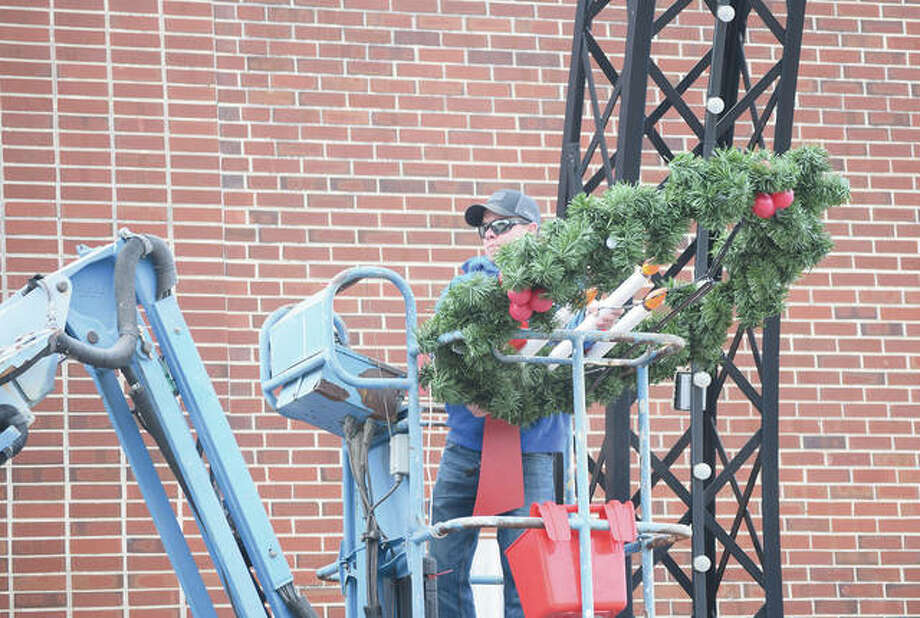 Jacksonville city employee John Guseman takes down holiday wreaths Monday that had been placed around the downtown square for Christmas. Photo: Marco Cartolano | Journal-Courier