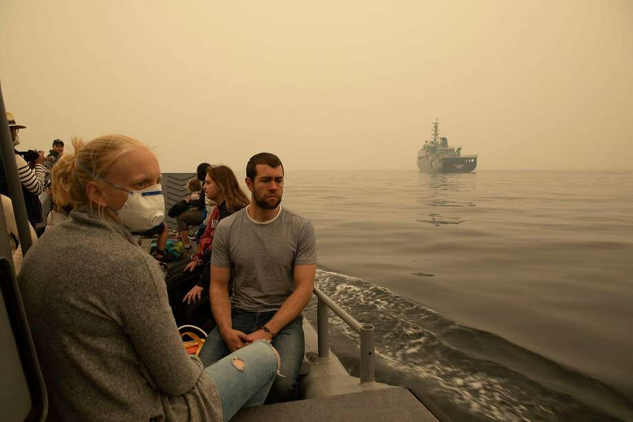 Residents evacuate from the town of Mallacoota in Victoria state by boat to a waiting Navy ship. Smoke from the wildfires has choked air quality and turned daytime skies to darkness. Photo: Royal Australian Navy / AFP