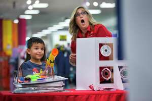 Paulina Killingbeck, J.C. Penny human resources supervisor, right, reacts to 6-yr-old Mason Gamboa's accuracy after he shot a toy gun shot while he was shopping at J.C. Penny at the Rim shopping center in San Antonio on Saturday, Aug. 10, 2019.