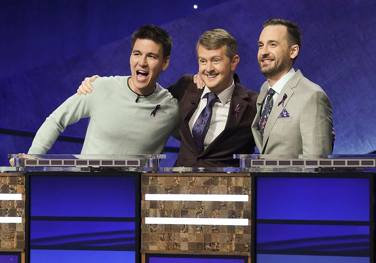 """In this image released by ABC, contestants, from left, James Holzhauer, Ken Jennings and Brad Rutter appear on the set of """"Jeopardy! The Greatest of All Time,"""" in Los Angeles. The all-time top """"Jeopardy!"""" money winners; Rutter, Jennings and Holzhauer, will compete in a rare prime-time edition of the TV quiz show which will air on consecutive nights beginning 8 p.m. EDT Tuesday. (Eric McCandless/ABC via AP)"""