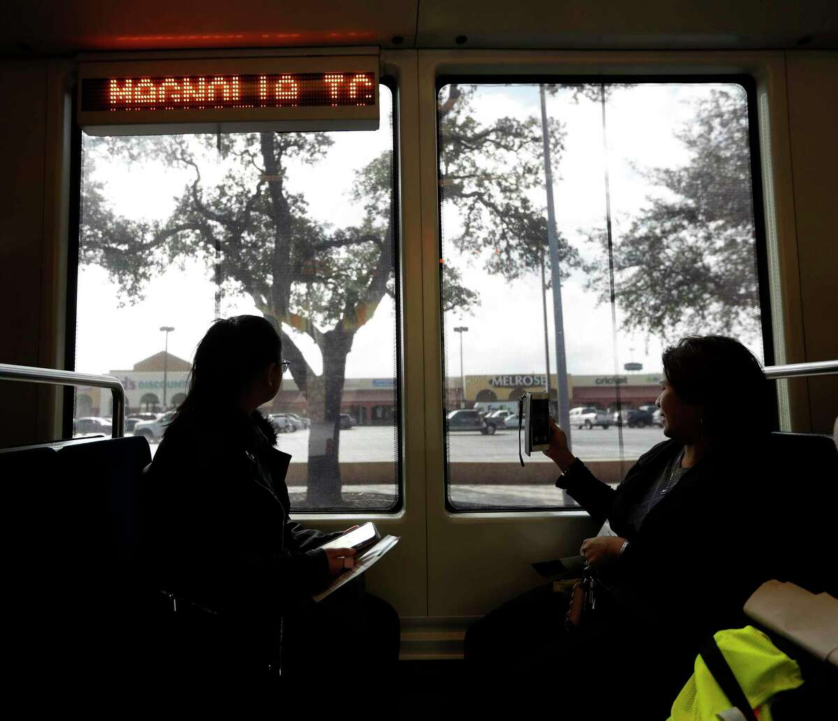 Tam Tran, left, and her mother Thuy Nguyen, right, look through the windows at a shopping center parking lot as they rode in the inaugural METRORail trip across the recently completed Harrisburg Overpass Bridge, Monday, January 9, 2017.