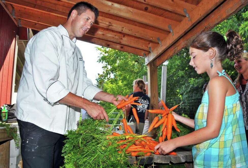 Noah Sheetz, executive chef at the Governor?s Mansion in Albany, and Julia Lettrick,9, a Goff Middle School student sort carrots at the school's Organic Garden and Farmer's Market in East Greenbush Wednesday morning August 11, 2010. (John Carl D'Annibale / Times Union)