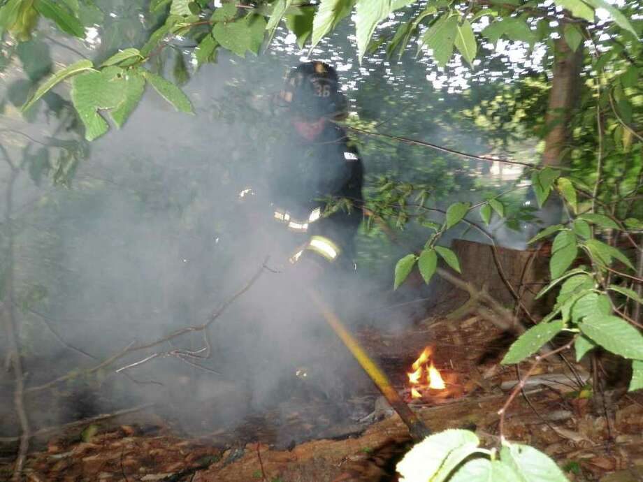 Westport firefighters douse flames that erupted Thursday in the woods off Imperial Avenue and Harbor View Road. Photo: Contributed Photo / Westport News