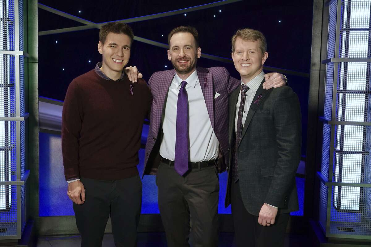 """In this image released by ABC, contestants, from left, James Holzhauer, Brad Rutter and Ken Jennings appear on the set of """"Jeopardy!"""" in Los Angeles. The all-time top money winners; Rutter, Jennings and Holzhauer, will compete in a rare prime-time edition of the TV quiz show """"Jeopardy! The Greatest of All Time,"""" which will air on consecutive nights beginning 8 p.m. EDT Tuesday. (Eric McCandless/ABC via AP)"""