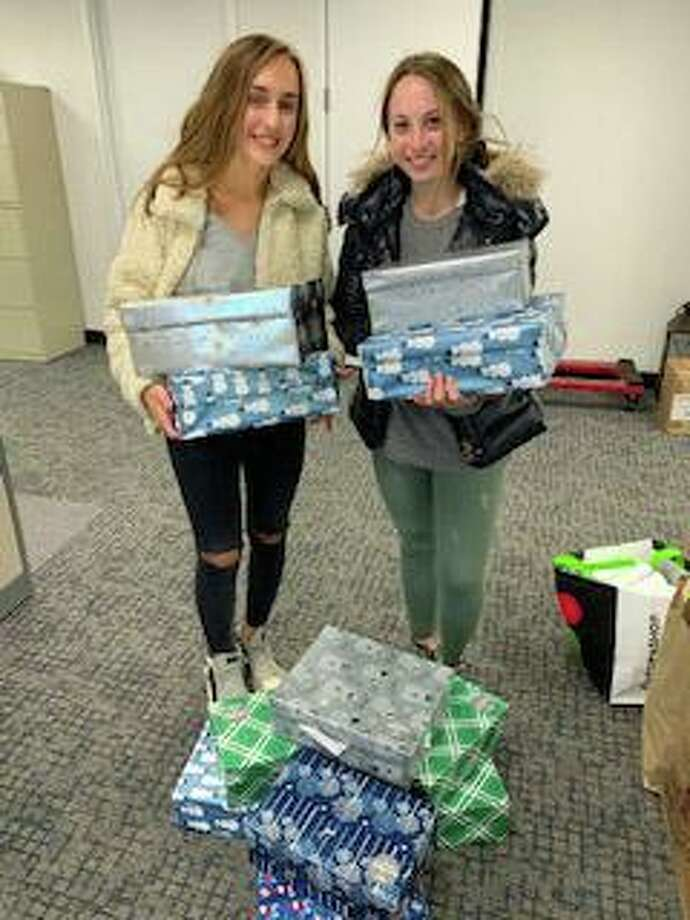 Staples High School juniors Arden Sherer, The Shoebox Project's club president, left, and Vice President Harley Bonn collected decorated shoeboxes filled with gifts for residents of Domestic Violence Crisis Center's two safe houses over the holidays. The students collect and distribute gifts in the form of decorated shoeboxes to women who are homeless or at-risk of homelessness in the area. Photo: Contributed