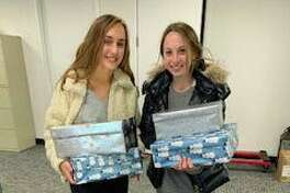 Staples High School juniors Arden Sherer, The Shoebox Project's club president, left, and Vice President Harley Bonn collected decorated shoeboxes filled with gifts for residents of Domestic Violence Crisis Center's two safe houses over the holidays. The students collect and distribute gifts in the form of decorated shoeboxes to women who are homeless or at-risk of homelessness in the area.