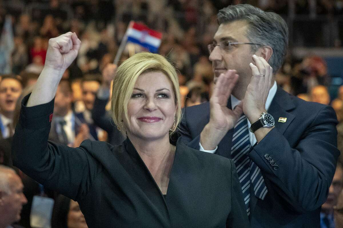 In this Thursday, Dec.19, 2019, file photo, presidential candidate Kolinda Grabar Kitarovic, left and prime minister Andrej Plenkovic greet supporters at a rally in Zagreb, Croatia. Croatia's bitterly contested presidential race is headed for a finale this weekend to decide whether a conservative or a liberal will lead the country during its first ever chairmanship over the European Union.