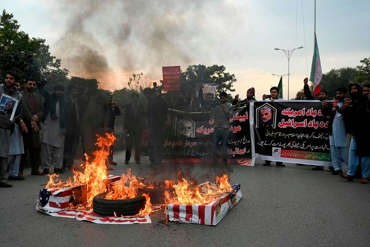 Protesters burn US flags as they shout slogans against the United States during a demonstration following a US airstrike that killed top Iranian commander Qasem Soleimani in Iraq, in Islamabad on January 3, 2020. - A US strike killed top Iranian commander Qasem Soleimani at Baghdad's international airport On January 3, dramatically heightening regional tensions and prompting arch enemy Tehran to vow