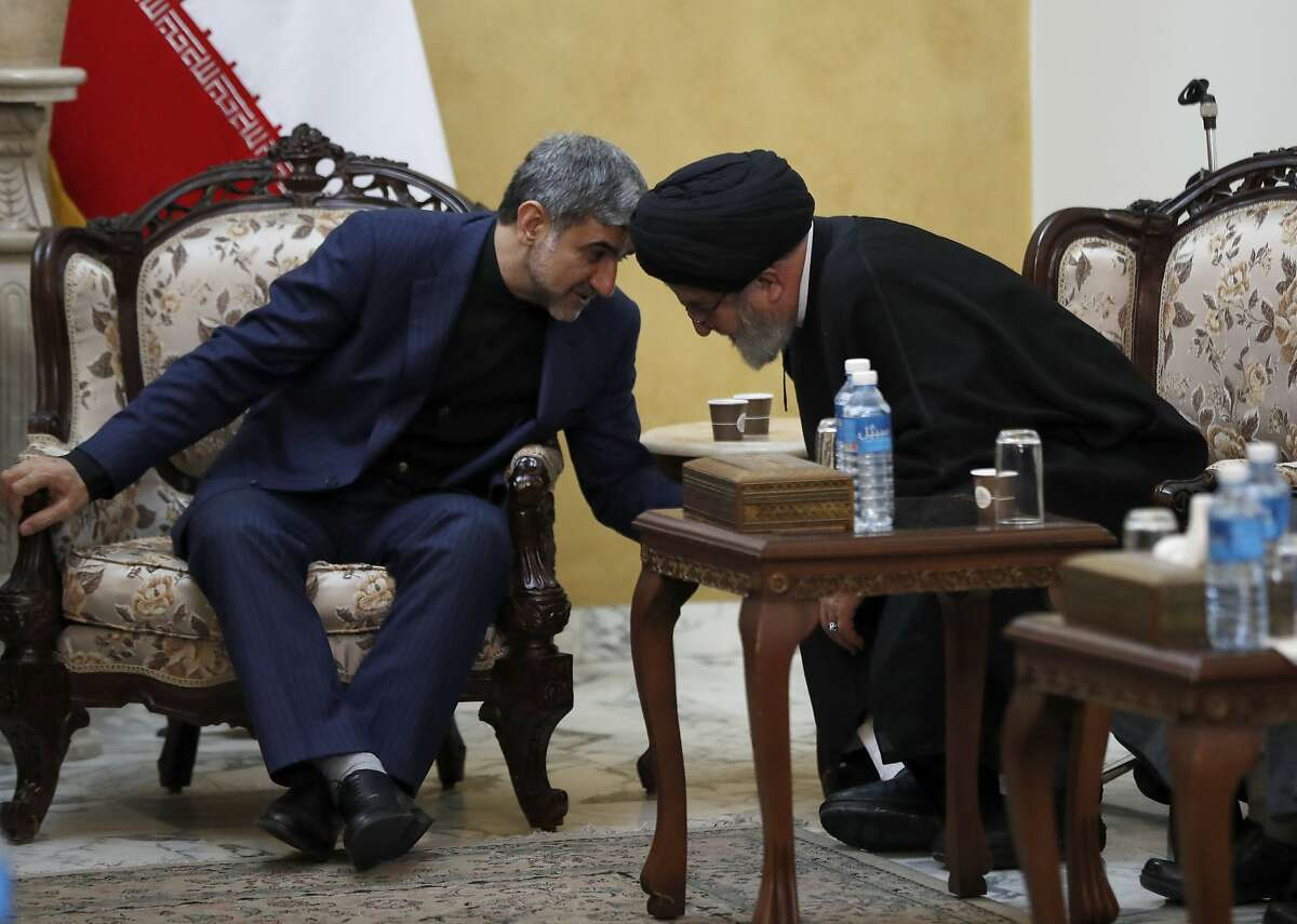 """Iran's Ambassador to Lebanon Mohammed Jalal Feiruznia, left, speaks with Ibrahim Amin al-Sayyed, head of Hezbollah political bureau, right, during the condolences of the Iranian Revolutionary Guard Gen. Qassem Soleimani, at the Iranian embassy, in Beirut, Lebanon, Friday, Jan. 3, 2020. President Donald Trump says the Iranian military commander who was killed by a U.S. airstrike in Iraq was """"plotting to kill"""" many Americans. (AP Photo/Hussein Malla)"""