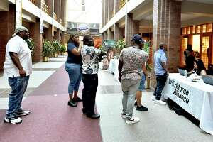 People line up to pre-register for interviews for positions at the Amazon North Haven distribution center, during a job fair at City Hall in New Haven, Conn., on Aug. 30, 2019. Three months later, Connecticut recorded a monthly of
