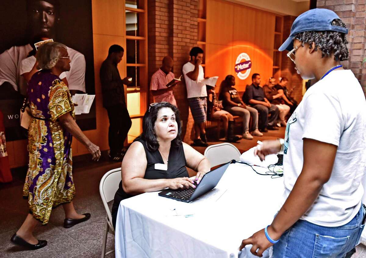 Ilsa Nieves of the American Job Center Workforce Alliance, left, pre-registers people for interviews for positions at the Amazon North Haven distribution center, during a job fair at City Hall in New Haven, Conn., on Aug. 30, 2019. Three months later, Connecticut recorded a monthly of
